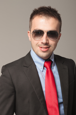 Portrait of young business wearing sunglasses, on grey studio background. photo