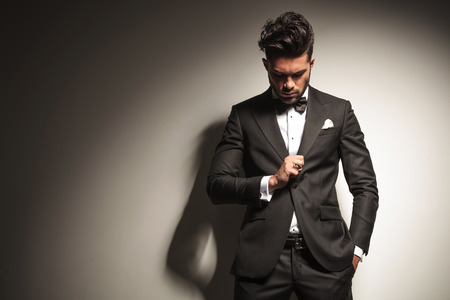 man looking down: Handsome young business man looking down to his ring while holding one hand in his pocket.