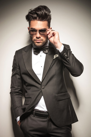 魅力的な若いビジネスの男が彼のポケットに 1 つの手を保持している間彼のサングラスを離陸します。 写真素材