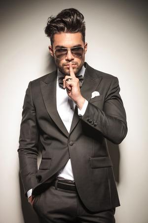 Jonge zakenman leunend op een muur waarop de stille gebaar terwijl die een hand in zijn zak.