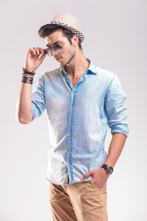 Young casual man holding one hand in his pocket while taking off his sunglasses, looking down. photo