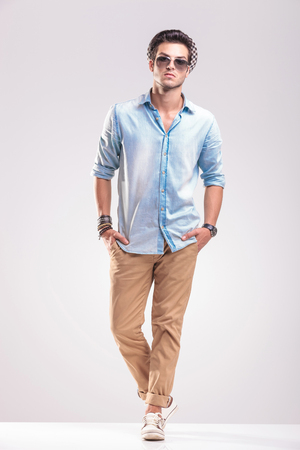 Handsome young casual man posing on grey background with both hands in his pocket. 免版税图像