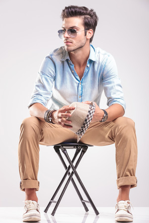 casual fashion: Young casual fashion man looking away while sitting on a stool, holding his hat in his hands.