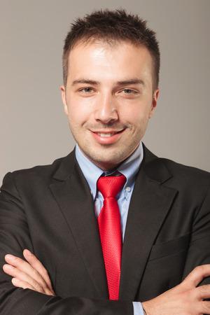 carita feliz: Sonriente joven hombre de negocios con los brazos cruzados sobre fondo gris de estudio.