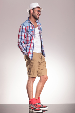 man side: Side view picture of a casual young man standing with his hands in pockets. Stock Photo