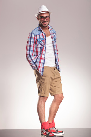 hand in pockets: Full length picture of a young casual man standing with his hand in pockets while smiling at the camera.