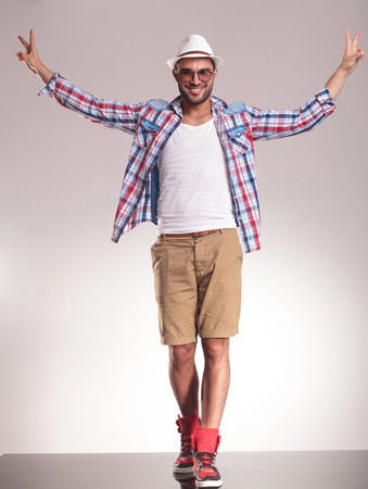 holding hands while walking: Happy young casual man walking while holding his hands up celebrating a victory. Stock Photo