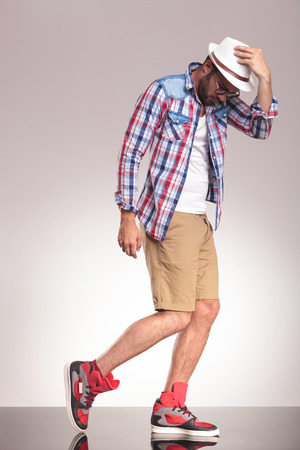 man looking down: Side view picture of a casual man walking on studio background holding his hand on his hat while looking down.