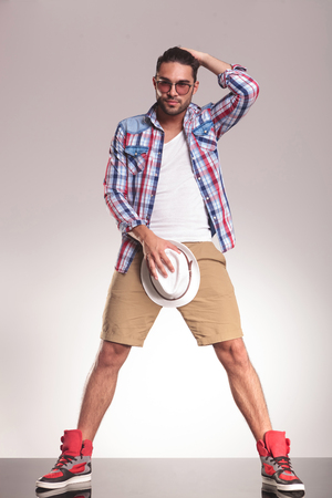 genitals: Full body picture of a casual youn man standing on studio backgroud, holding his hat to his crotch while the other one is in his hair.