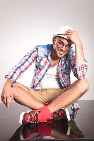 legs crossed at knee: Young fashion man sitting on the floor with his legs crossed, resting one hand on his knee while holding his hat with the other one.
