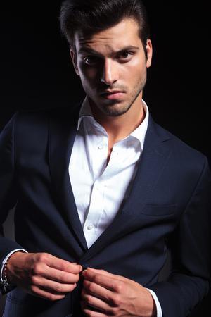 cerrando negocio: Cierre de imagen de un hombre de negocios joven y guapo cerrar su chaqueta mientras mira a la c�mara.