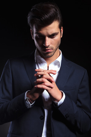 man looking down: Elegant young business man looking down while holding his hand together, praying.