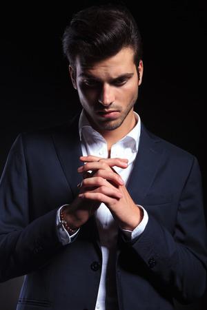 hombre orando: Elegante joven hombre de negocios mirando hacia abajo mientras sostiene la mano juntos, orando.