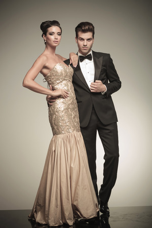 gown: Picture of a young elegant couple posing together, the woman is holding her hand on her waist while the man is fixing his jacket. Stock Photo