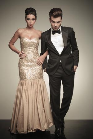 Полное тело картина элегантной пары ходить на фоне студии. Человек смотрит в то время как держа обе руки в карманы. Фото со стока