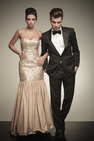 evening gown: Full body picture of a elegant couple walking on studio background. The man is looking down while holding both hands in his pockets.