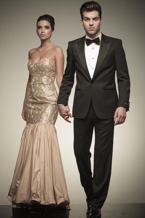 魅力的なエレガントな男の彼の恋人の手を握っている間スタジオの背景の上を歩いてします。
