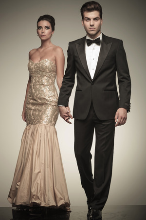 tuxedo: Attractive elegant man walking on studio background while holding his lover hand. Stock Photo