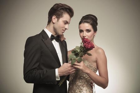 lazo regalo: Hombre joven hermoso que da a su esposa un ramo de rosas rojas, mientras que ella está mirando a la cámara. Foto de archivo