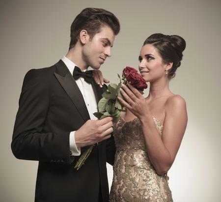 roses rouges: Mari offrant sa belle �pouse un bouquet de roses rouges, ils sont � la recherche les uns les autres. Banque d'images