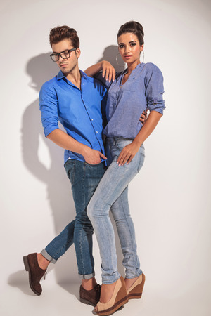 Full body picture of a young fashion couple posing on studio background. Stock Photo