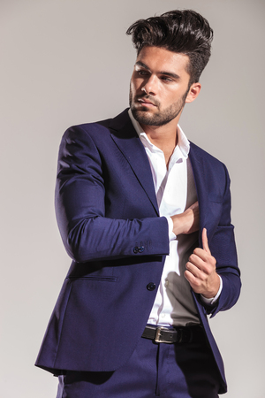 put away: Stylish young business man looking away from the camera while putting something inside his jacket.