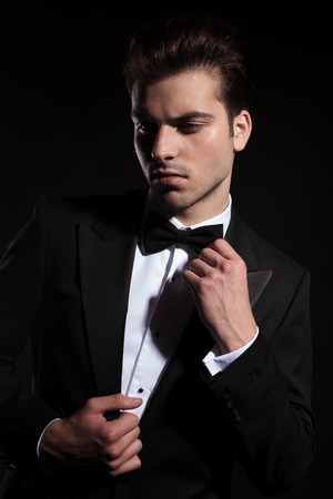 man looking down: Young business man looking down while fixing his jacket and bowtie.