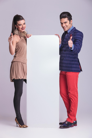 Fashion couple holding a white board while showing the thumbs up gesture. photo