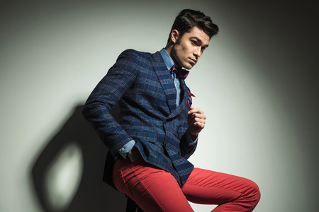 man looking down: Side view of a handsome fashion man looking down while sitting on a chair with his hand in pocket.