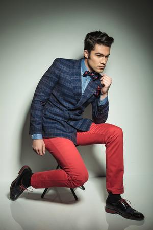 jambes �cart�es: Corps entier d'un jeune homme de mode beau assis sur une chaise, les jambes �cart�es. Banque d'images