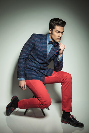 modelos hombres: Foto de cuerpo entero de un hombre de moda joven hermoso que se sienta en una silla con las piernas separadas.