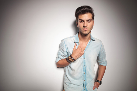 lean on hands: Cool young fashion man leaning on studio background while holding one hand in his pocket and pulling his shirt.