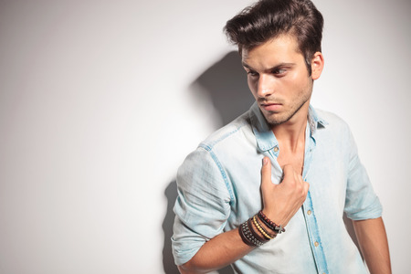 style man: Close up picture of a handsome man pulling his shirt while looking down. Stock Photo