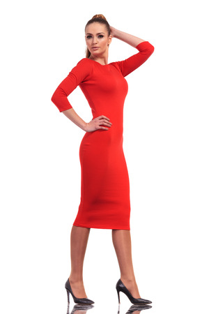 Attractive fashion woman wearing a slim red dress walking on studio background. photo