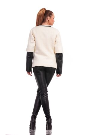 women in boots: Rear view of a young fashion woman standing with her legs crossed on isolated background. Stock Photo