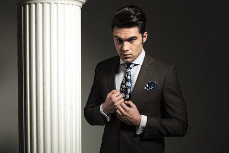 Portrait of a young business man fixing his collar while looking at the camera. photo