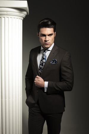 Young business man holding one hand in his pocket while fixing his suit. photo
