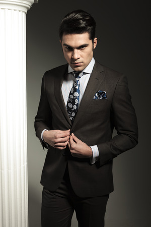cerrando negocio: Hombre de negocios joven cerrando su chaqueta mientras mira a la c�mara. Foto de archivo