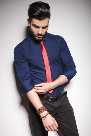 man looking down: Young business man looking down while fixing his sleeve. Stock Photo