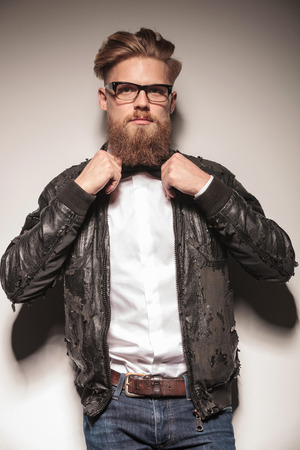 Hipster business man fixing his bowtie while looking at the camera. Stock Photo