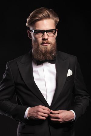 cerrando negocio: Elegante joven hombre de negocios mirando a la cámara mientras se cierra la chaqueta. Foto de archivo