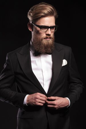 man looking down: Picture of a elegant business man looking down while closing his jacket.