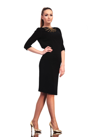 hands on waist: Side view of a young elegant business woman posing on isolated studio backgound with one hand on her waist. Stock Photo