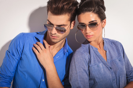 Close up picture of a casual fashion couple looking down, on studio background. photo