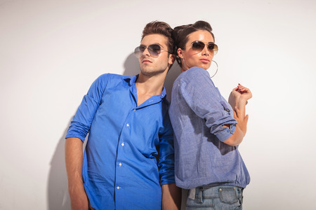 Down view of a casual couple posing together while leaning on a grey wall. photo