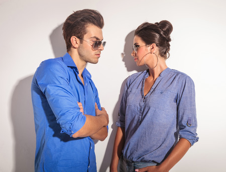 Casual couple looking at each other while leaning on a grey wall. photo