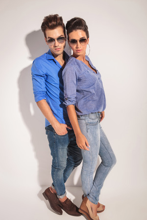 poses: Full body picture of a casual couple posing on studio background.