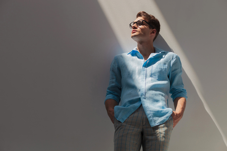 hand in pockets: Portrait of a handsome young casual man leaning on a grey wall while holding his hand in pockets.