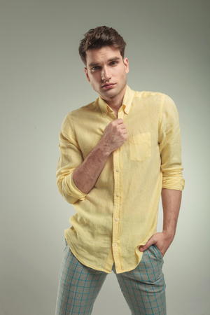 buttoning: Young casual man standing on studio background with his hand in pocket while opening his shirt.