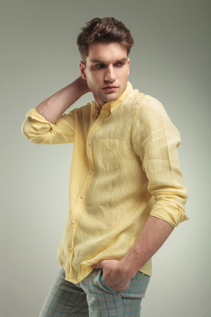 man looking down: Side view of a young fashion man looking down while holding his hand in pocket.